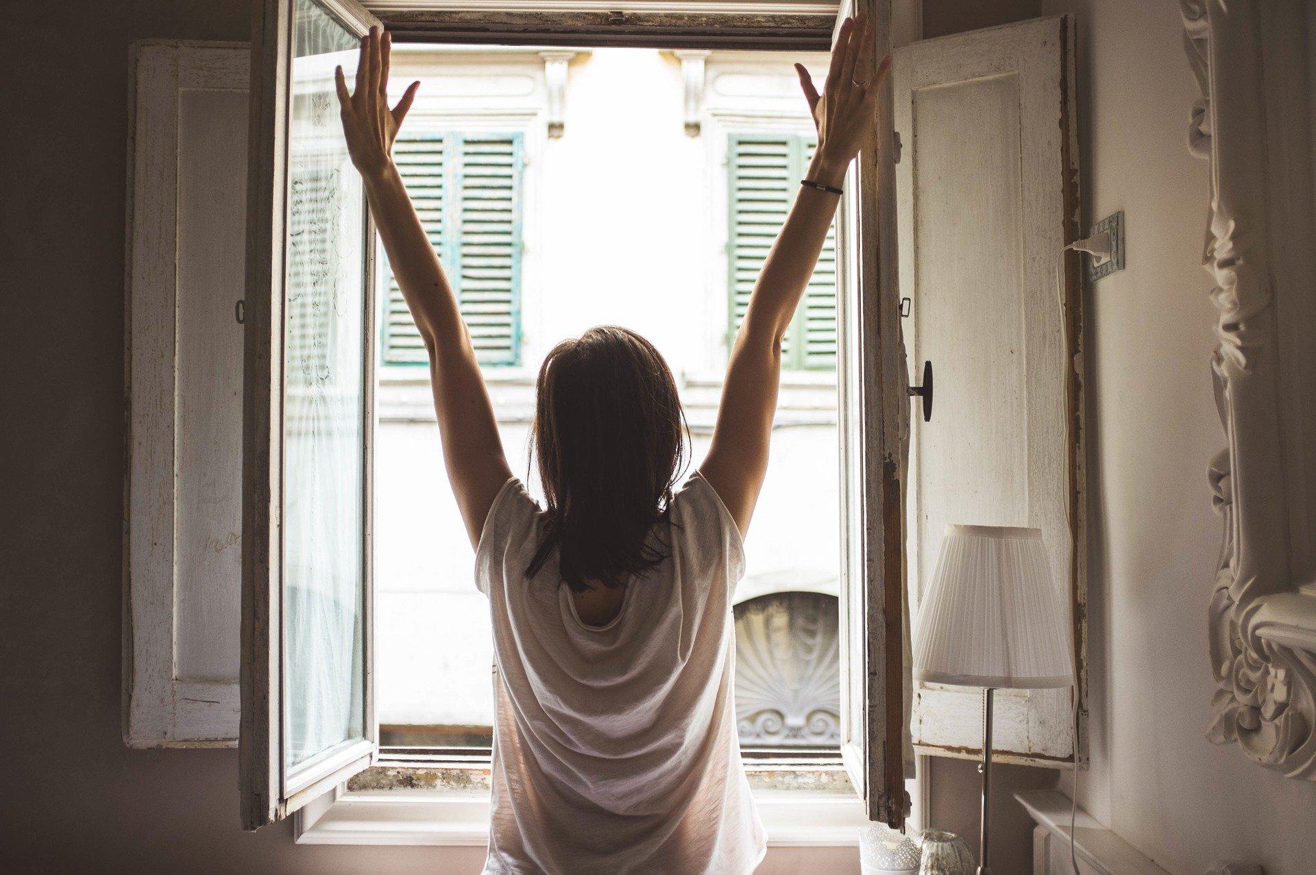 mujer abriendo las ventanas de casa